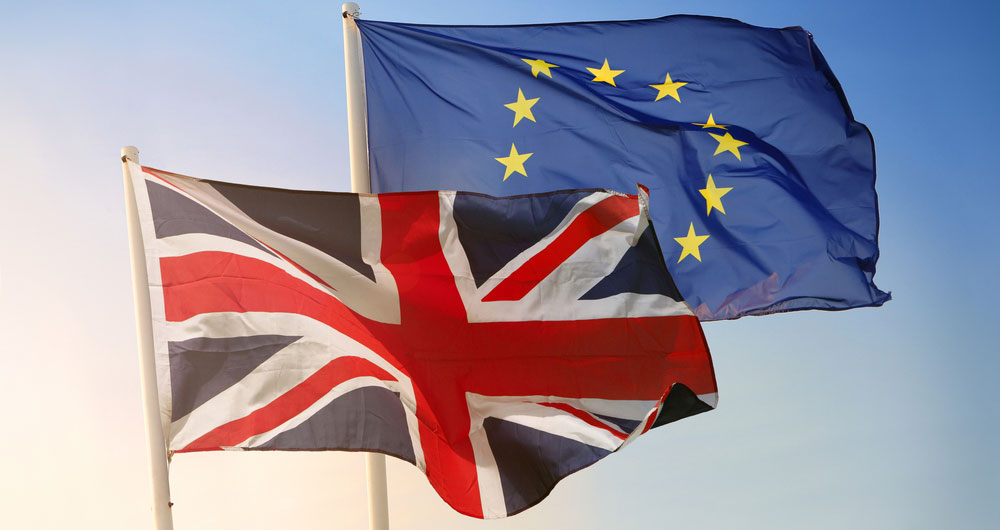 EU and UK flags flutter against a pale blue sky