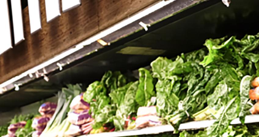 A photograph of vegetables on a supermarket shelf