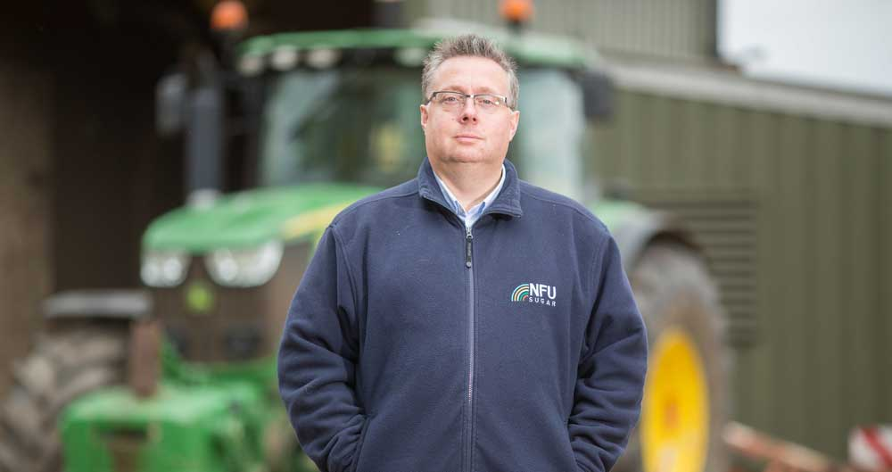 NFU Sugar Board Chairman Michael Sly standing in front of his tractor