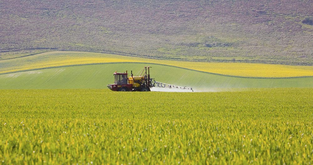 A picture of a tractor spraying crops in a field.