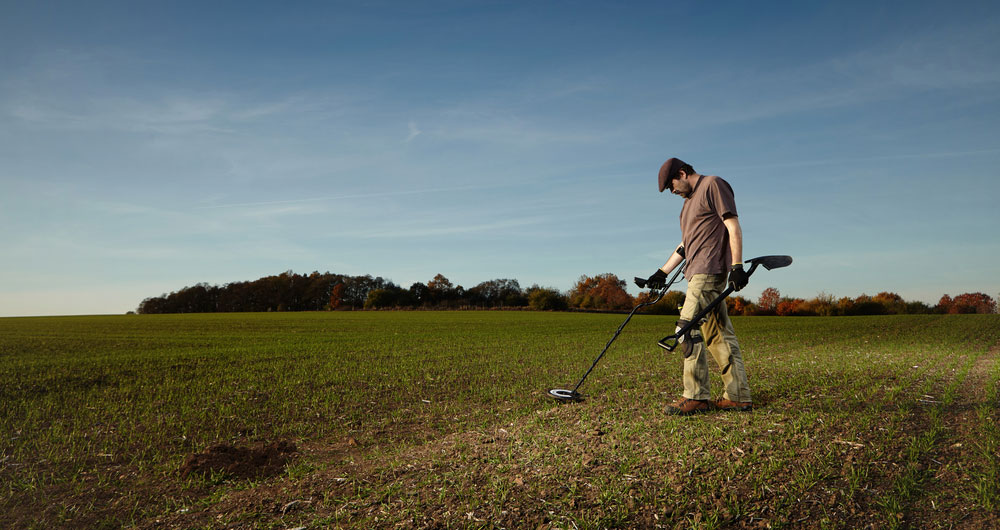 Metal detectorist on farmland