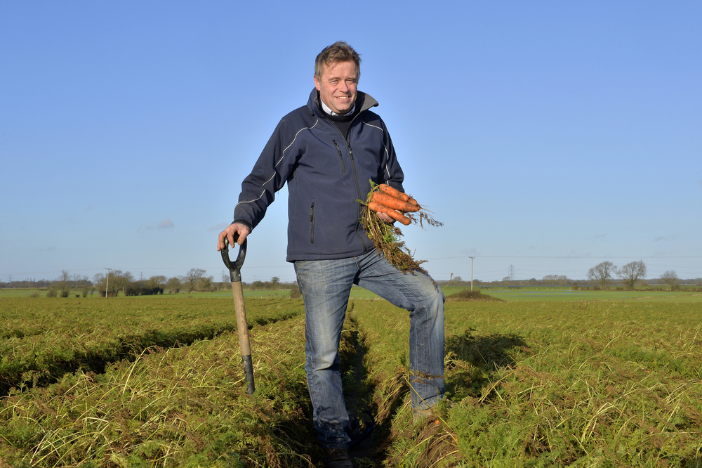 Guy Poskitt, on his farm in Yorkshire, holding a bunch of carrots, leaning on a fork