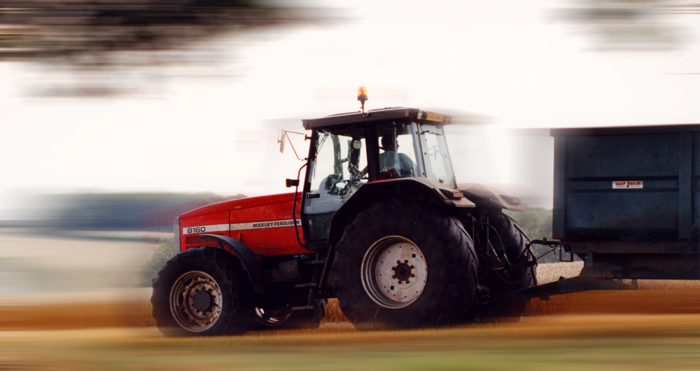 A tractor moving at speed pulling a trailer