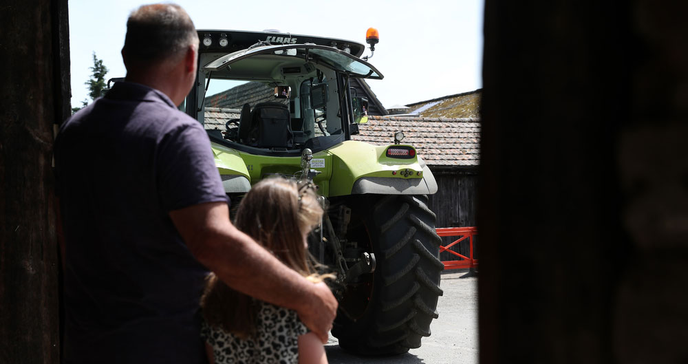 Farmer with his arm around a child while watching a tractor work