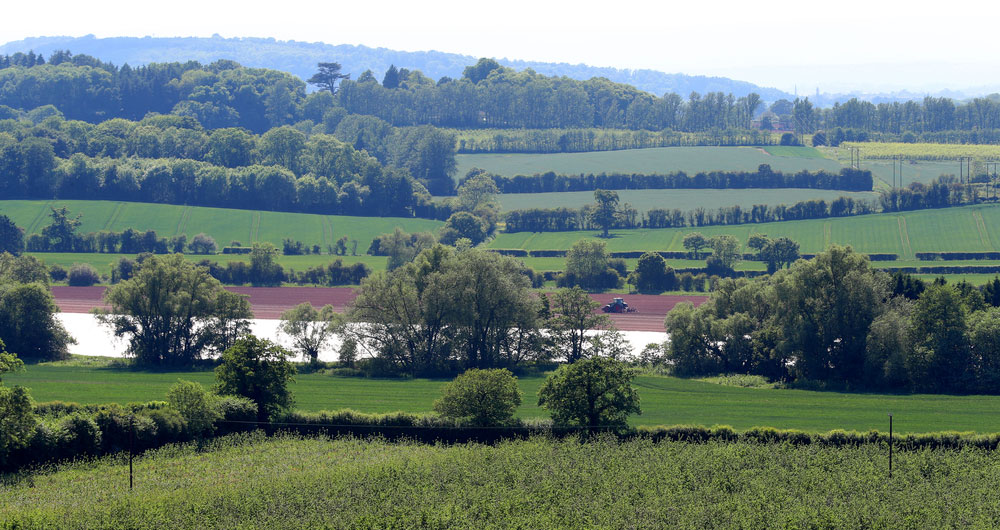 A Herefordshire farming landscape with a distant tractor working the land