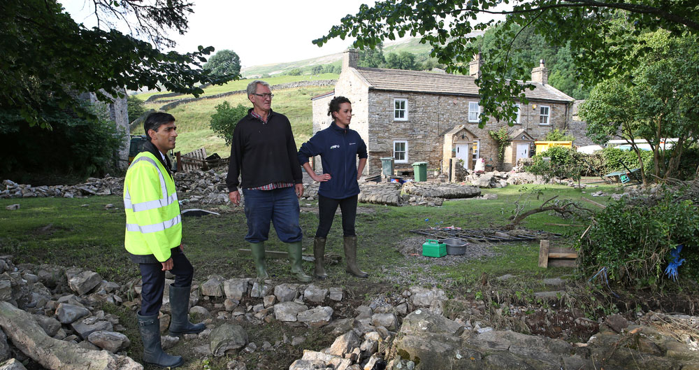 Dales floods - Rishi Sunak MP surveys the devastation with farmer Raymond Calvert and group secretary, Lindsey-Anne Murfin