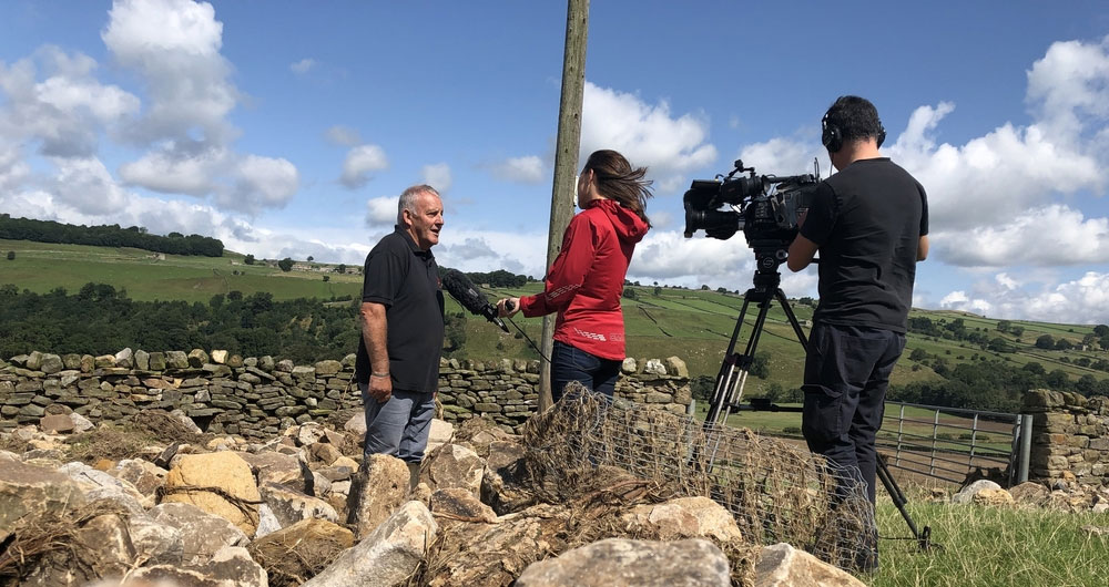 Dales farmer Mike Barker being interviewed by BBC Look North surrounded by stone deposited on his fields by the floods
