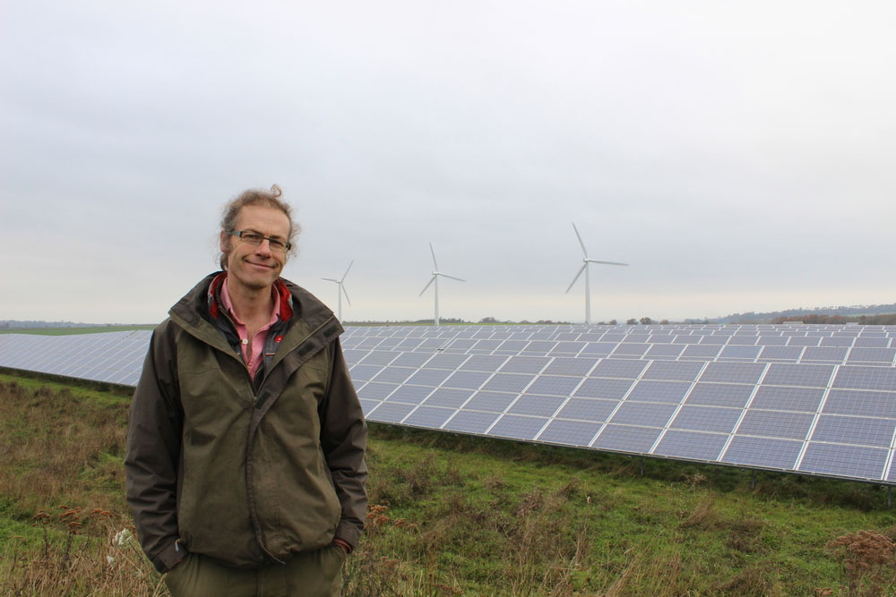 An image of NFU member Adam Twine pictured in front of solar panels on farm