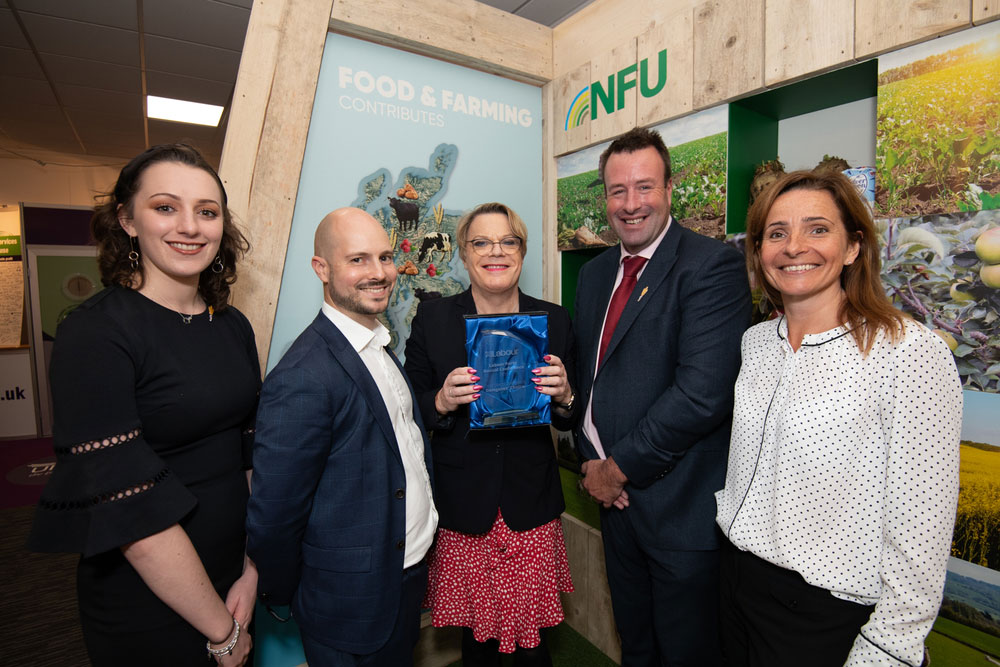 Eddie Izzard pictured presenting the award to NFU Vice President Stuart Roberts, director of communications Fran Barnes and external affairs colleagues Rocky Lorusso and Emma Crosby.