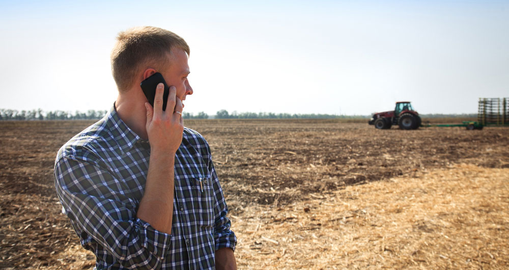 man on phone in field with tractor