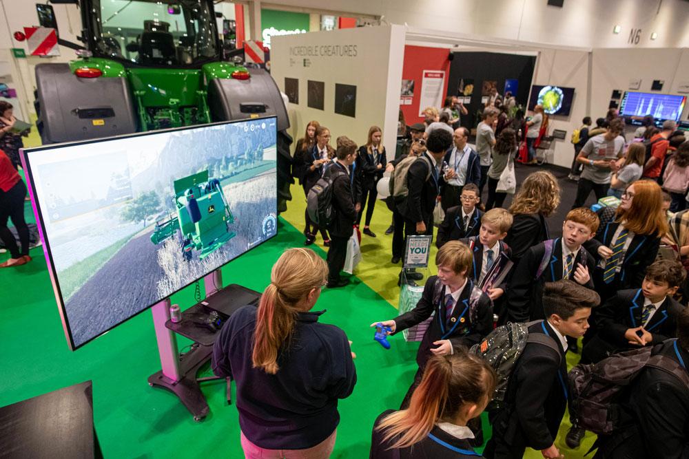 Georgina Barratt, NFU Student and Young Farmer Ambassador, talks schoolchildren through the farming simulator at the Future of Farming exhibit at New Scientist Live, Excel, 10 October 2019