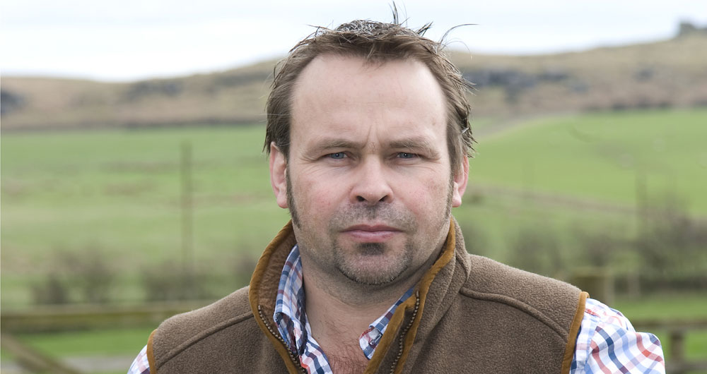 Simon Bainbridge standing on his farm