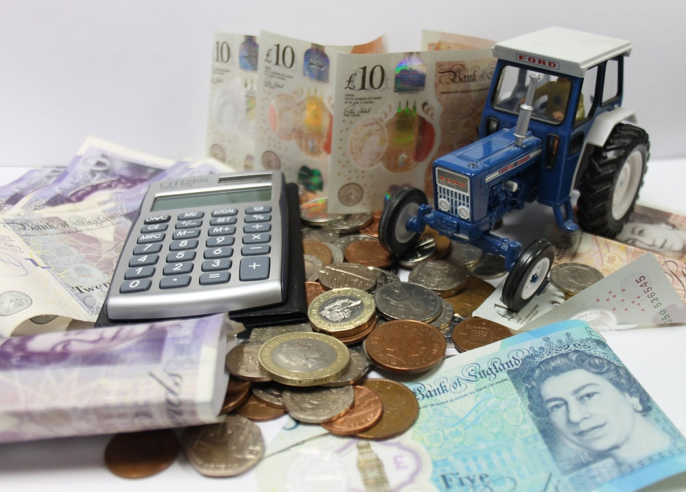 A pile of cash with a miniature tractor and calculator