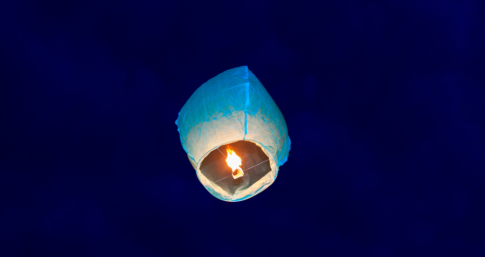 A single sky lanterns in the night sky