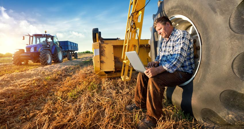 A farmer using a laptop on farm