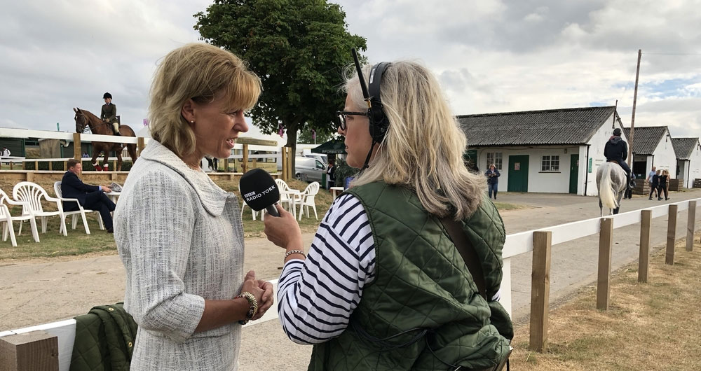 Minette Batters standing ringside at the Great Yorkshire Show being interviewed by Radio York