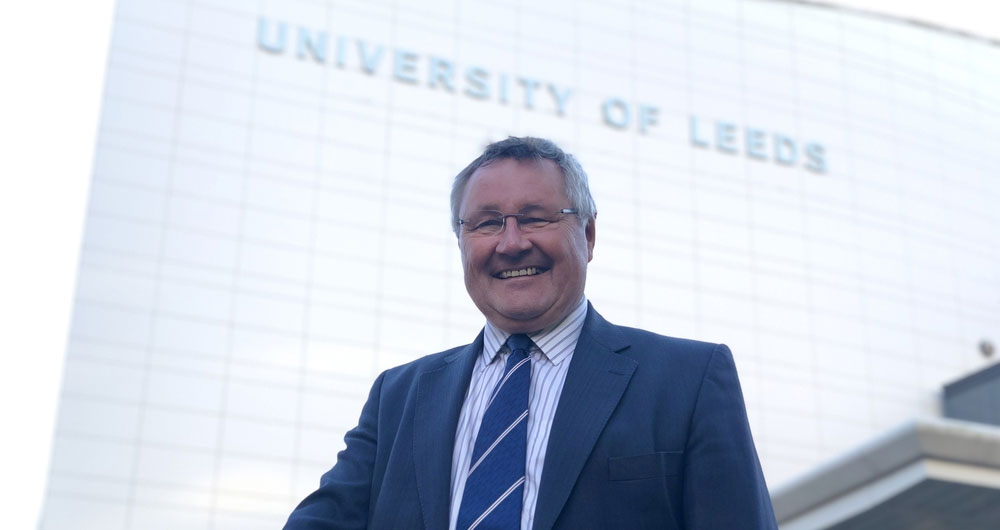 Tim Bennet standing with large, glass fronted University of Leeds building behind