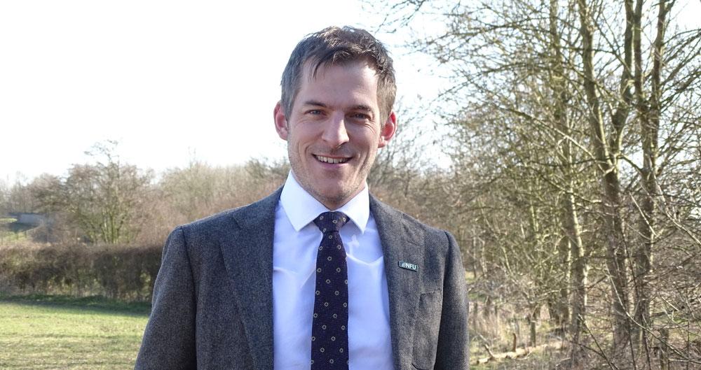 Adam Bedford standing in a field of arable crops